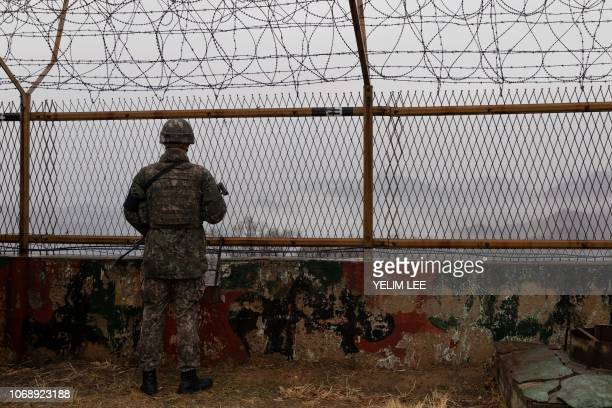 In a photo taken on December 3 2018 a South Korean soldier stands before a security fence at a guard post inside the Demilitarized Zone near the...