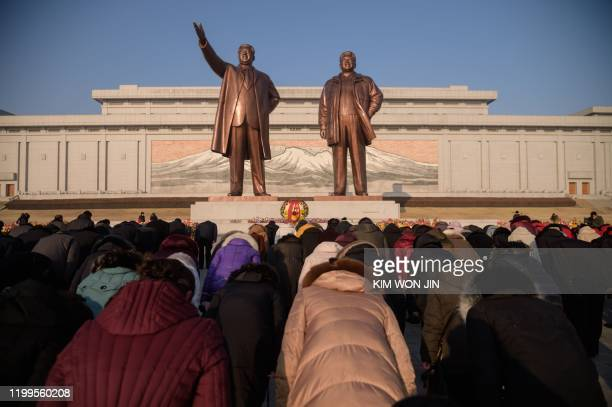 TOPSHOT In a photo taken on February 8 2020 people bow before the statues of late North Korean leaders Kim Il Sung and Kim Jong Il on Mansu Hill to...