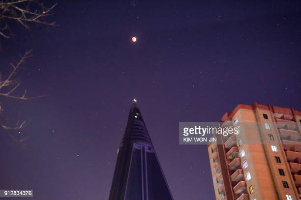 TOPSHOT In a photo taken on January 31 2018 a 'super blood blue moon' rises above the landmark Ryugyong hotel in Pyongyang The cosmic event not seen...