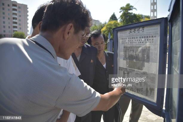TOPSHOT In a photo taken on July 1 2019 people read a newspaper showing coverage of a meeting between US president Donald Trump and North Korea's...