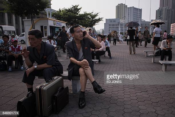 In a photo taken on July 11 a man talks on a mobile phone as he sits in a public square in Pyongyang / AFP / Ed Jones