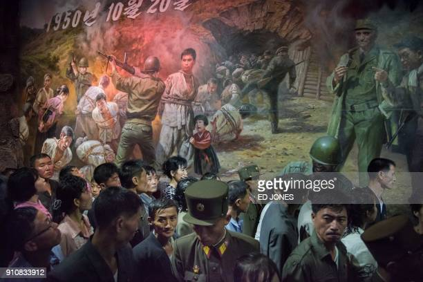 TOPSHOT In a photo taken on July 24 2017 North Korean visitors walk past a painting showing US soldiers preparing to kill North Koreans at the...