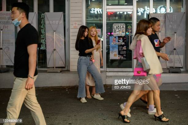 In a photo taken on July 4 2020 two women take photos on a street in Chuncheon