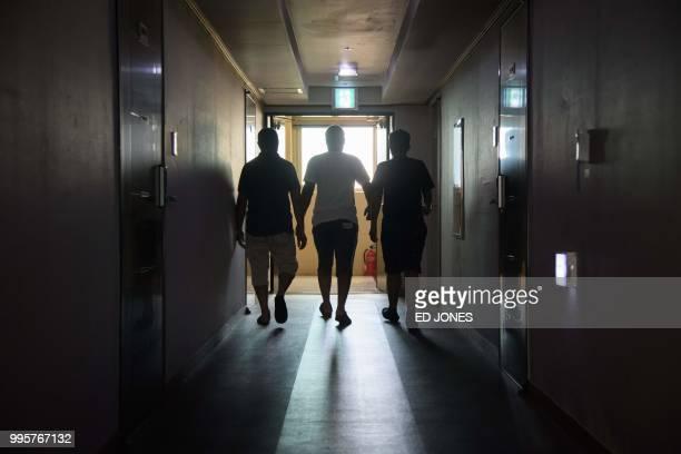In a photo taken on July 4 a group of Yemeni asylum seeker walk along a hallway of the Olle Tourist Hotel in Jeju A few hundred asylumseekers from...