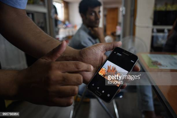 In a photo taken on July 4 Yemeni asylum seeker Mohammed Salem Duhaish shows an image of a bomb blast in the Yemeni capital of Sana'a on his mobile...