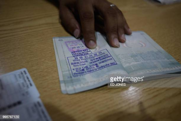 In a photo taken on July 4 Yemeni asylum seeker Mohammed Salem Duhaish shows a South Korean visa in his passport in Jeju A few hundred asylumseekers...