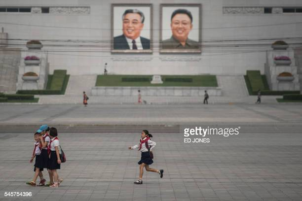 TOPSHOT In a photo taken on July 9 2016 a child runs before the portraits of former North Korean leaders Kim IlSung and Kim JongIl in Pyongyang / AFP...