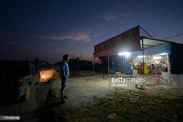 In a photo taken on June 12 2013 a man stands outside a roadside shop near Beihai in southwestern China's Guangxi province Widely reported to be the...