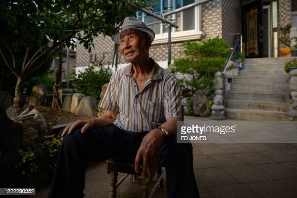 In a photo taken on June 17 North Korean refugee Kim Kunwook sits outside his home in the 'Abai village' area of Sokcho On a cold winter's day in...