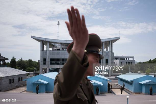In a photo taken on June 2 2017 a Korean People's Army soldier gestures as he stands before the military demarcation line separating North and South...