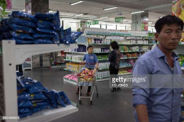 In a photo taken on June 4 2017 a boy pushes a shopping cart at the Kwangbok or 'liberation' department store in Pyongyang / AFP PHOTO / Ed JONES