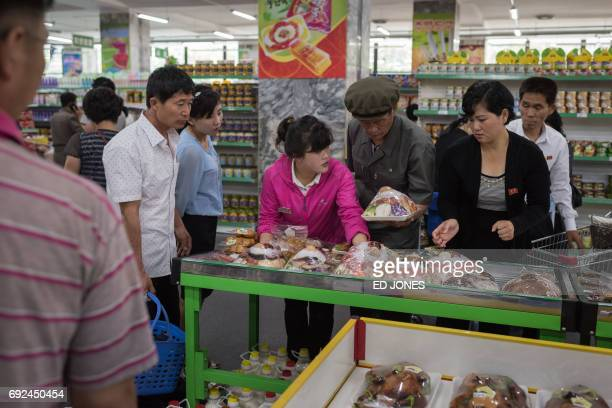 In a photo taken on June 4 2017 a staff member assists shoppers at the Kwangbok or 'liberation' department store in Pyongyang / AFP PHOTO / Ed JONES