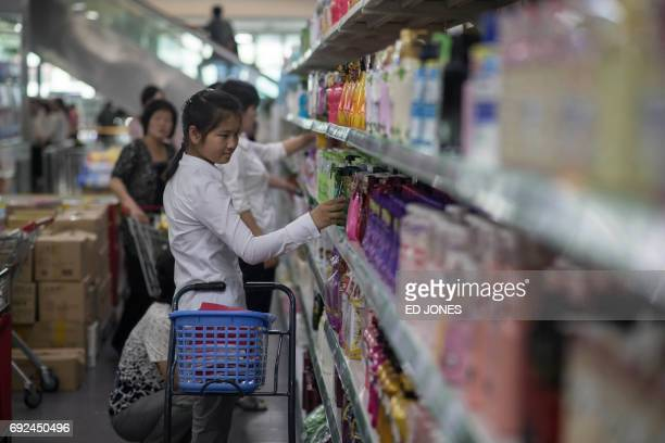 In a photo taken on June 4 2017 a woman checks products on display at the Kwangbok or 'liberation' department store in Pyongyang / AFP PHOTO / Ed...