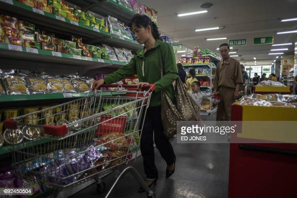 In a photo taken on June 4 2017 a woman pushes a shopping cart at the Kwangbok or 'liberation' department store in Pyongyang / AFP PHOTO / Ed JONES