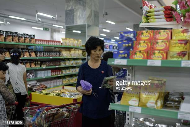 In a photo taken on June 4 2017 customers shop for North Koreanproduced food at the Kwangbok department store supermarket in Pyongyang / To go with...