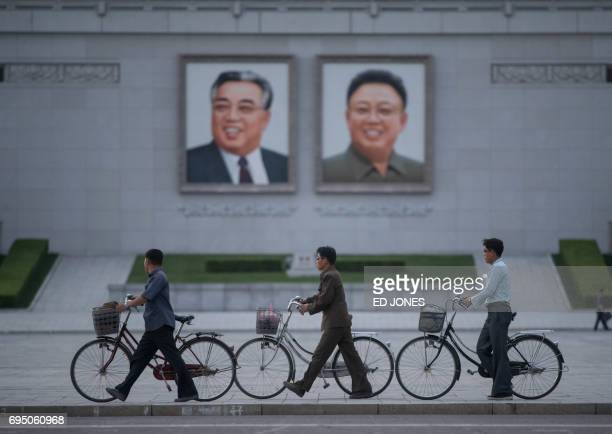 TOPSHOT In a photo taken on June 4 2017 men push their bicycles past the portraits of late North Korean leaders Kim IlSung and Kim JongIl on Kim...