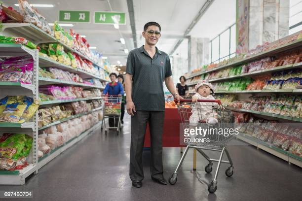 In a photo taken on June 4 2017 shopper Han GwangRim poses for a portrait with his daughter Su Ryon at a supermarket in Pyongyang / AFP PHOTO / Ed...
