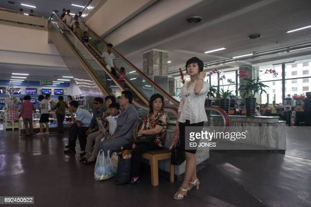 In a photo taken on June 4 2017 shoppers gather at the entrance of the Kwangbok or 'liberation' department store in Pyongyang / AFP PHOTO / Ed JONES