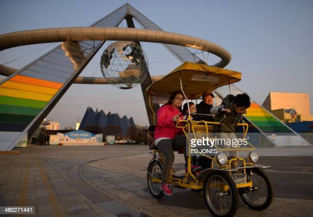In a photo taken on March 22 2014 a family pass before the entrance to the 'Expo Science Park' the site of the 1993 world expo in Daejeon South Korea...