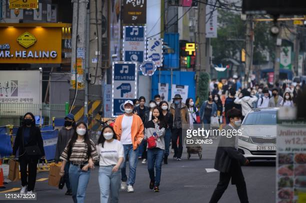 In a photo taken on May 10 people wearing face masks walk along a street in the Hongdae district of Seoul. - South Korea announced its highest number...