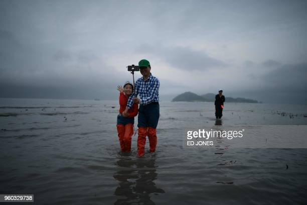 In a photo taken on May 18 2018 a man and child pose for a selfie as they return from the sea during an annual extreme low tide event during the...