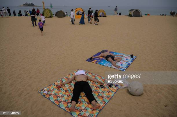 TOPSHOT In a photo taken on May 2 2020 holidaymakers sunbathe on a beach in Sokcho on South Korea's northeast coast during a public holiday long...
