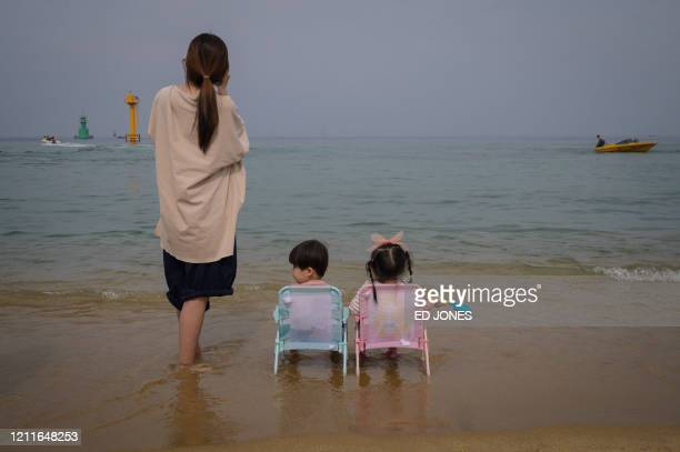 TOPSHOT In a photo taken on May 2 2020 holidaymakers visit a beach in Sokcho on South Korea's northeast coast during a public holiday long weekend
