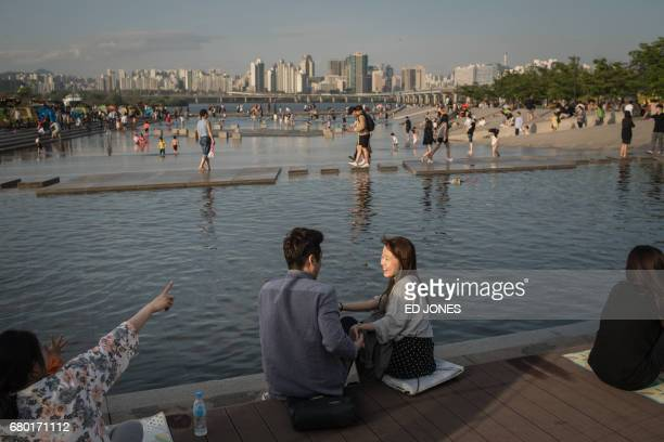 TOPSHOT In a photo taken on May 5 2017 a young couple sit next to a water feature before the Han river and the city skyline at Yeouido park in Seoul...