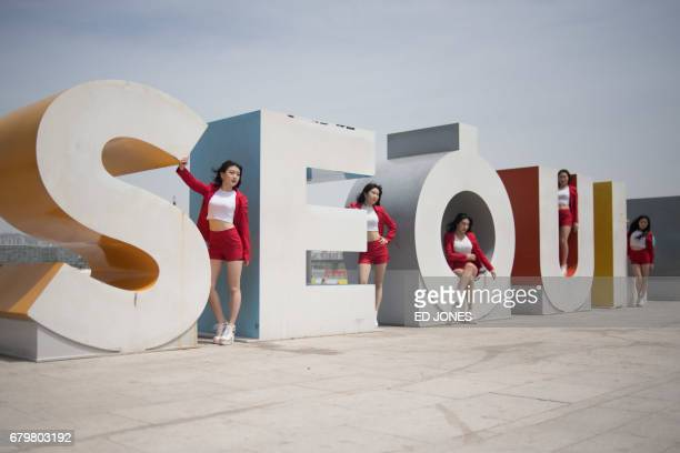 In a photo taken on May 6 2017 an amateur kpop group pose for photos before a sculpture prior to an impromptu concert at Yeouido park in Seoul When...