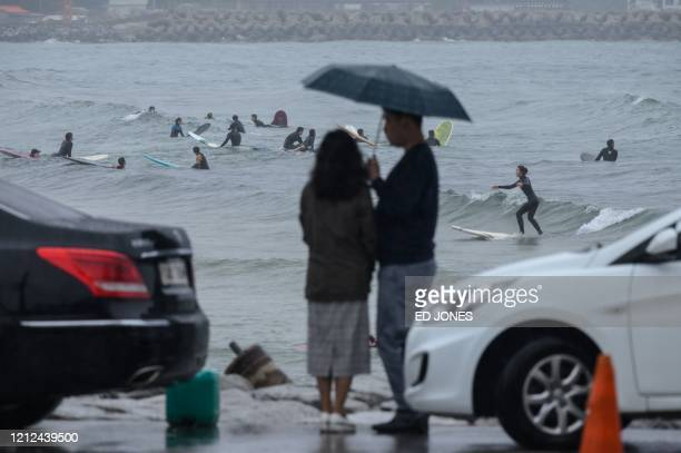 In a photo taken on May 9 2020 a couple watches surfers waiting to catch waves at Jukdo beach near Sokcho