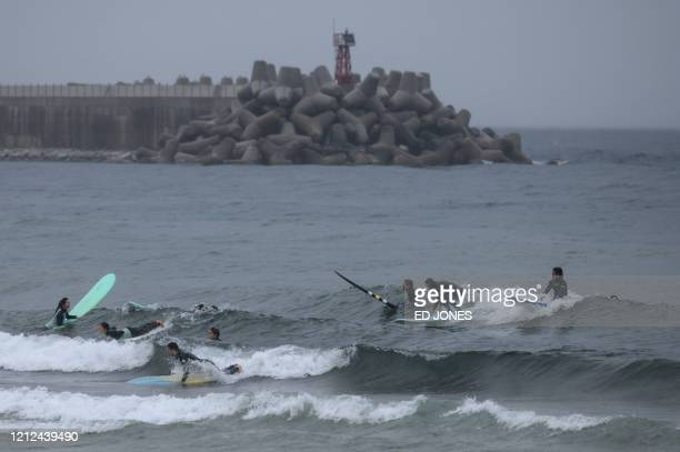 In a photo taken on May 9 2020 surfers gather in the water at Jukdo beach near Sokcho