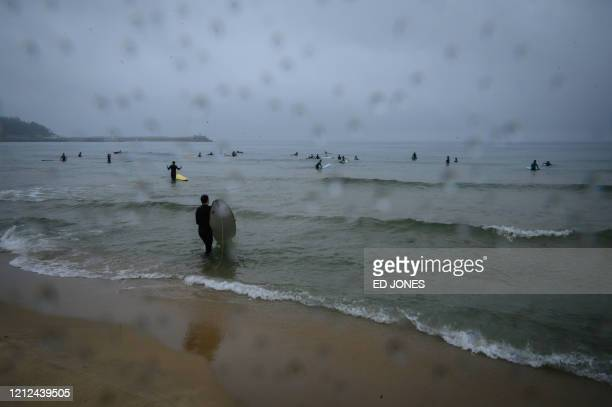 In a photo taken on May 9 2020 surfers make their way into the water at Jukdo beach near Sokcho