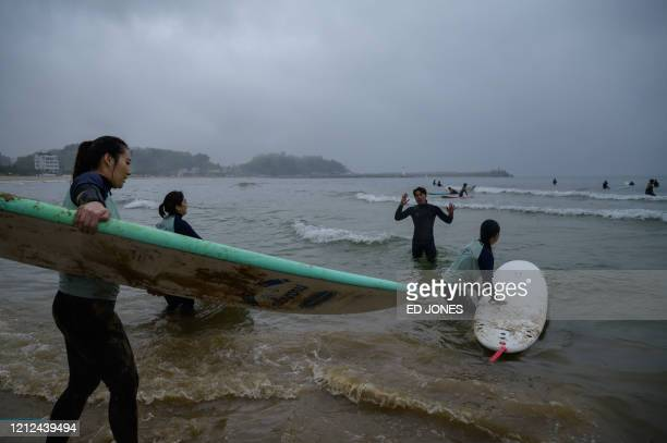 In a photo taken on May 9 2020 surfing students make their way into the water at Jukdo beach near Sokcho