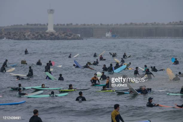 TOPSHOT In a photo taken on May 9 surfers gather in the water at Jukdo beach near Sokcho