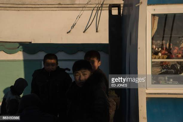 In a photo taken on November 19 children stand on a roadside on the outskirts of the industrial city of Chongjin on North Korea's northeast coast /...