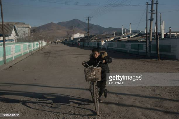 In a photo taken on November 21 a boy pushes a bicycle on a street on the outskirts of the industrial city of Chongjin on North Korea's northeast...