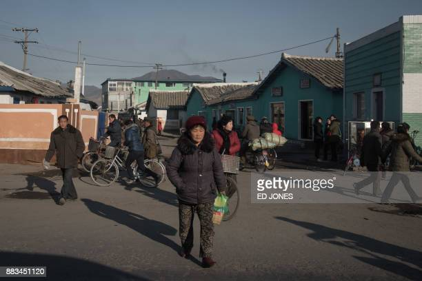 In a photo taken on November 21 people cross a street on the outskirts of the industrial city of Chongjin on North Korea's northeast coast / AFP...