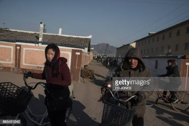 In a photo taken on November 21 people push bicycles across a street on the outskirts of the industrial city of Chongjin on North Korea's northeast...