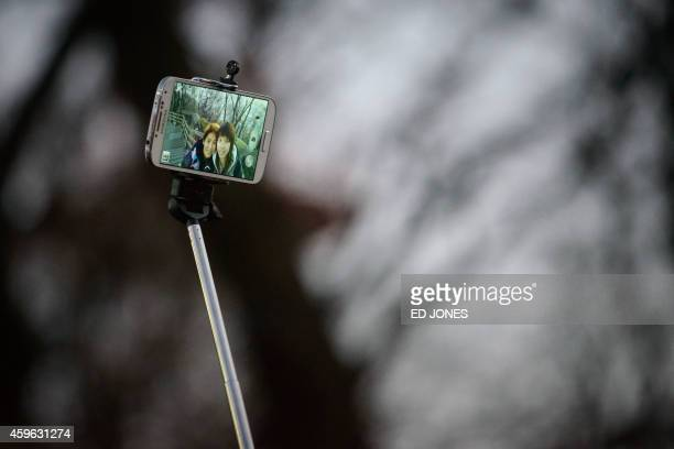 In a photo taken on November 26 2014 a couple use a 'selfie stick' to take a photo at a popular tourist spot in Seoul In South Korea anyone selling...
