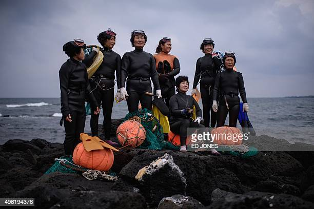 In a photo taken on November 6 2015 a group of 'Haenyeo' pose for photographers as they perform a demonstration during a media event organised by the...