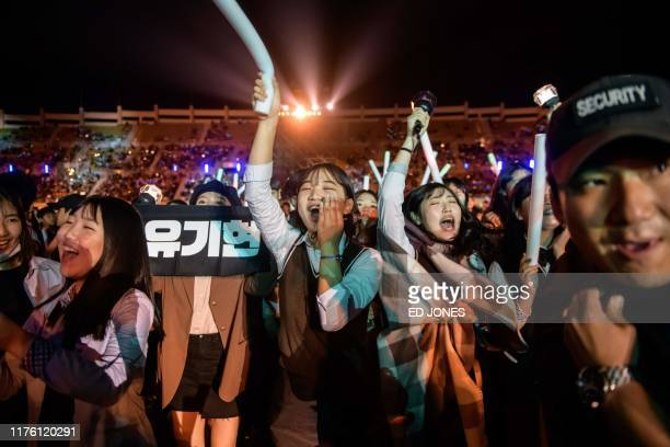 In a photo taken on October 11 audience members cheer for a professional Kpop band performing between rounds of amateurs at the 'Kpop World Festival'...