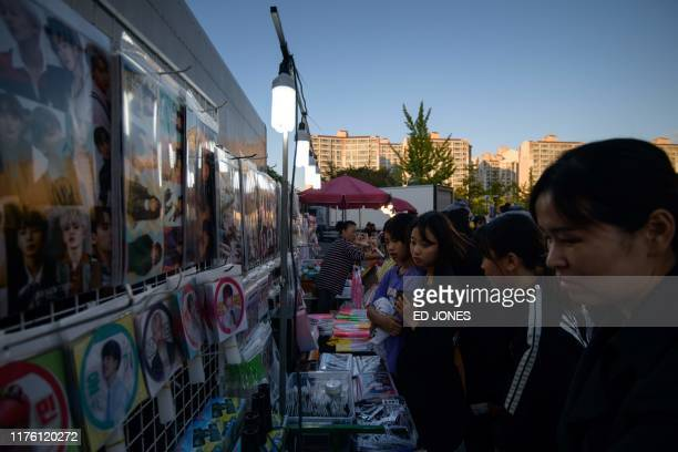 In a photo taken on October 11 spectators look at a Kpop merchandise stall outside a stadium at the 'Kpop World Festival' in Changwon At the grandly...