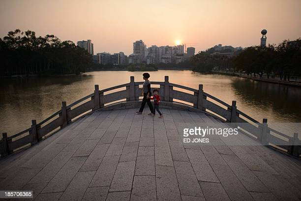 In a photo taken on October 22 2013 a woman and child walk across a bridge in a park in Fuzhou Fujian province Fuzhou is the capital of China's...