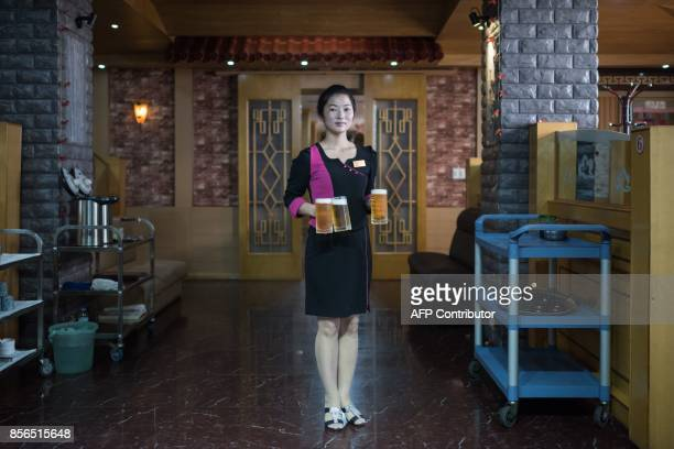 In a photo taken on September 26 2017 wait staff Li JinJu poses for a portrait at the Arrirang bar and restaurant in Pyongyang / AFP PHOTO / Ed JONES