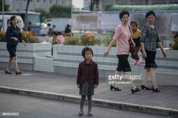 In a photo taken on September 27 2017 a child stands on a roadside in Pyongyang / AFP PHOTO / Ed JONES