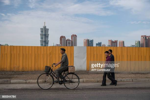 In a photo taken on September 27 2017 a cyclist and pedestrians pass along a street before the city skyline of 'Mirae Scientists Street' in Pyongyang...