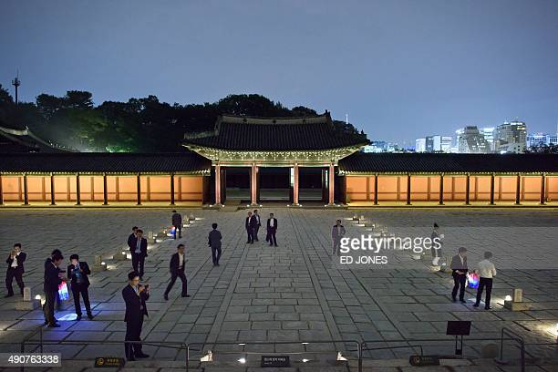 In a photo taken on September 30 2015 visitors walk in a courtyard during a moonlight tour at Changdeokgung Palace in Seoul The 15th century...