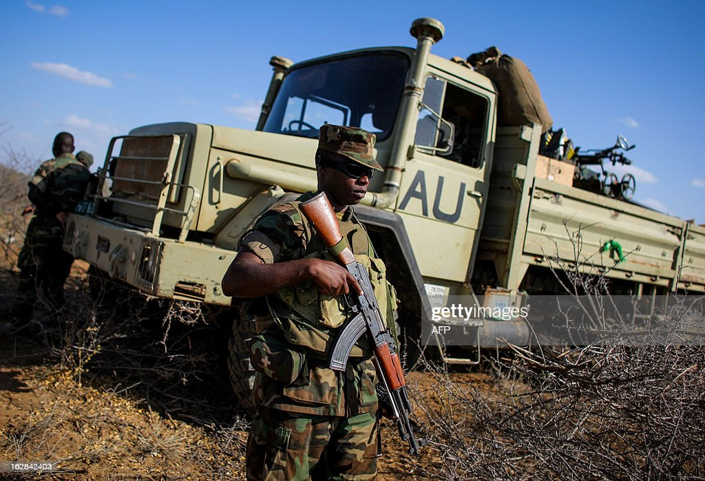 CREDIT 'AFP PHOTO / AU-UN IST PHOTO / STUART PRICE' - NO MARKETING NO ADVERTISING CAMPAIGNS - DISTRIBUTED AS A SERVICE TO CLIENTS In a photograph taken and released by the African Union-United Nations Information Support team on February 28, 2012, a Ugandan soldier serving with the African Union Mission in Somalia (AMISOM) stands in front of truck at a defensive position east of the central Somali town of Buur-Hakba following it's capture the day before from the Al-Qaeda-affiliated extremist group Al Shabaab by the Somali National Army (SNA), supported by AMISOM forces. The strategically important town linking the capital Mogadishu and the hinterlands of central Somalia was liberated without a shot being fired, marking a significant loss for the group. The town, located 64kms east of Baidoa, Somalia's second city, was a stronghold of the Shabaab where they extorted high levies of illegal taxation on the local civilian populations and used it as a base from where they planned and launched attacks against government forces and installations, AMISOM and the Somali population.