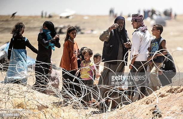 In a picture taken from Akcakale in Turkey Syrian refugees gesture as they ask for water at the Turkish border near the Syrian town of Tal Abyad on...