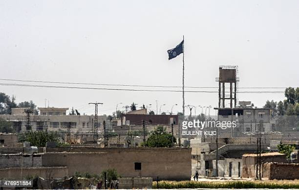 In a picture taken from Alcakale Turkey a flag of the Islamic State flutters amongst buildings in the center of the Syrian city Tal Abyad on June 13...